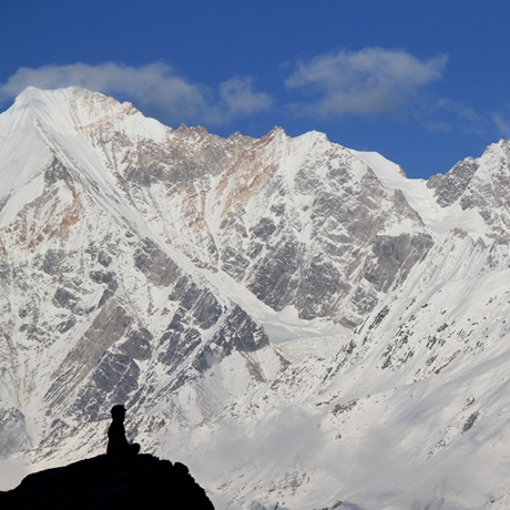 A silhouetted student sitting on a ledge looks out at the surrounding snowy mountain peaks of the Himalaya in India.