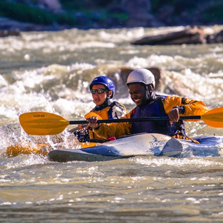 A student breaks into a huge smile after kayaking down a rapid.