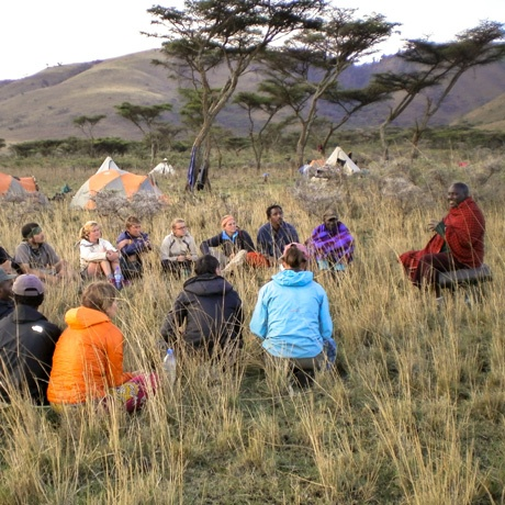 Students sitting in a circle listen to a local villager speaking in East Africa.