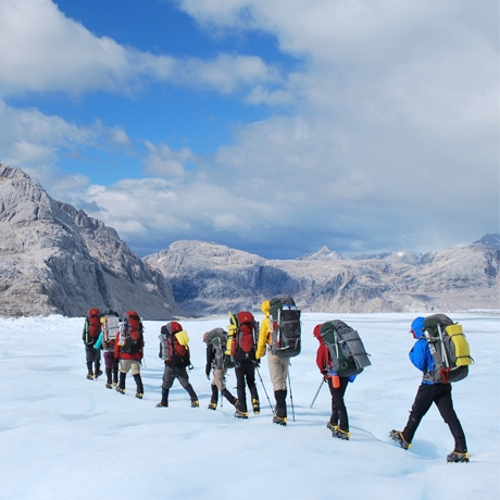 Students use crampons to backpack across a snowy field surrounded by mountains in Patagonia.