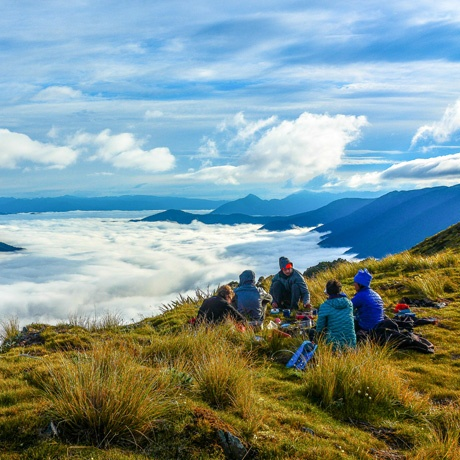 Course participants sit on a grassy ridge above the clouds in Kahurangi National Park.