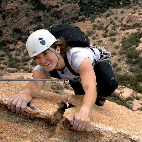 An instructor smiles as they reach the top of a pitch while rock climbing in the Southwest.