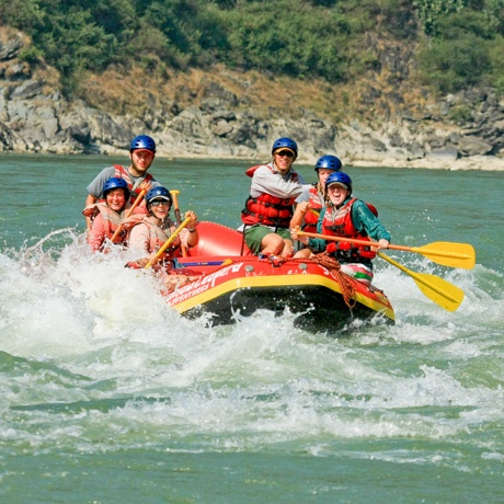 Students have fun in the rapids while whitewater rafting in India.