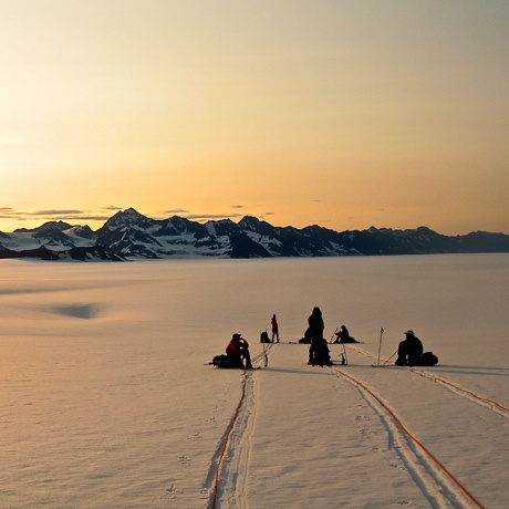 Students take a short break to watch the sunset before skinning through the night in Alaska's Chugach National Forest.
