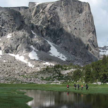 Students backpack past towering cliff faces in the Rocky Mountains.