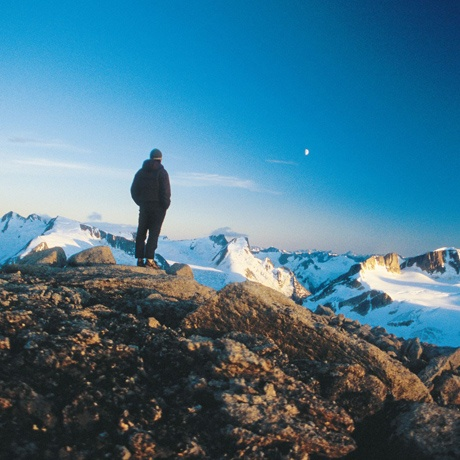 A student on a rocky ridge gazes out at the surrounding snowy mountains during sunrise in the Yukon.