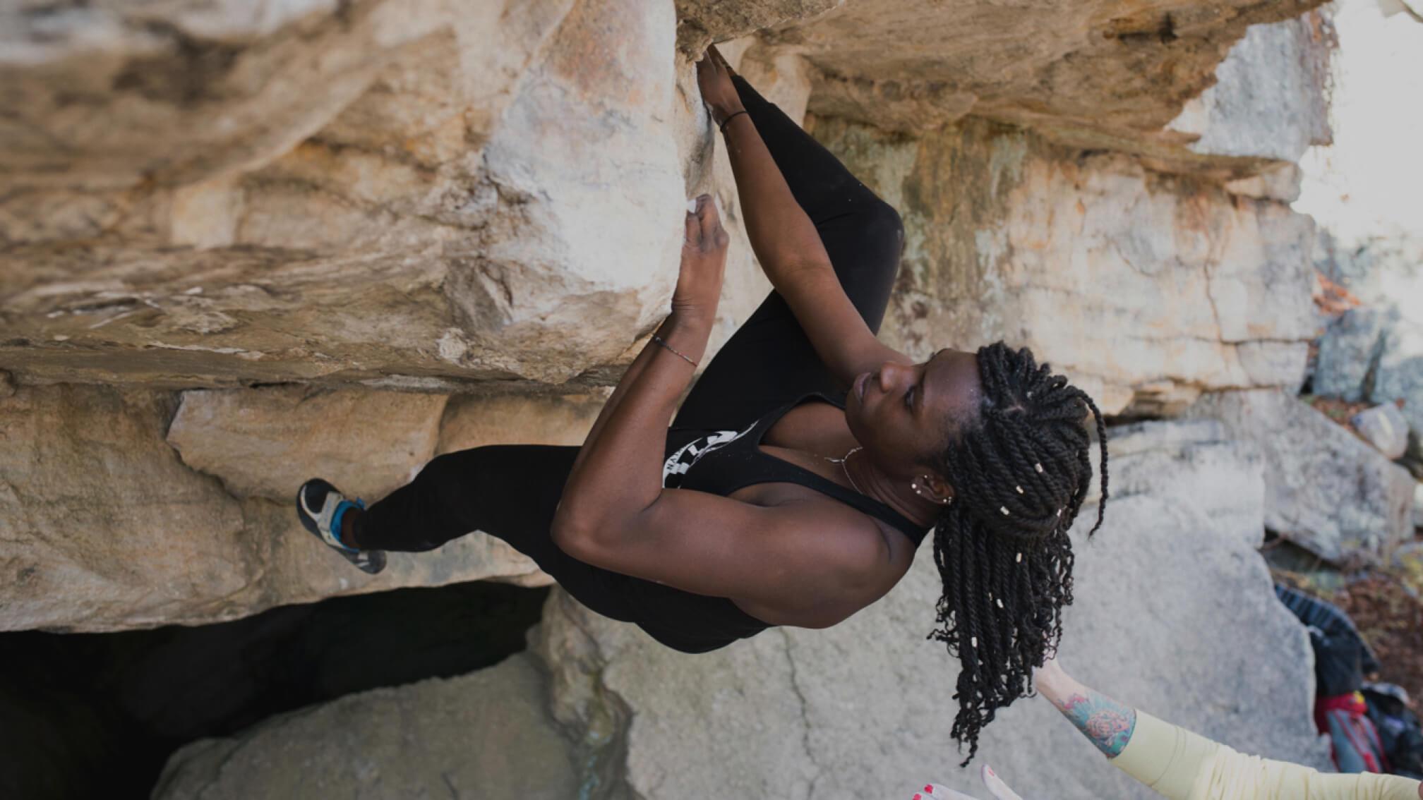 A climber bouldering on an overhang.