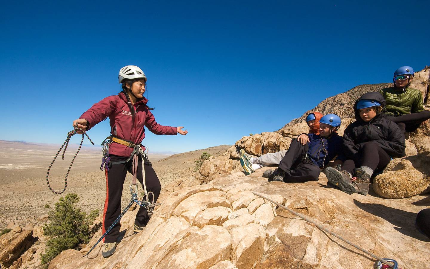 Students sitting on a rock ledge listen to an instructor's climbing lesson in the northern Rockies.